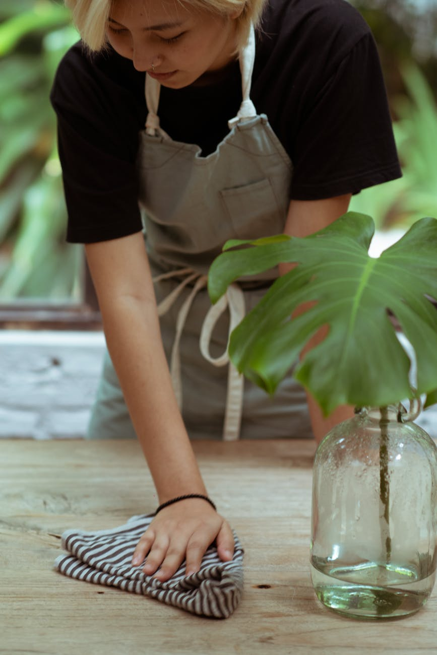 calm waitress wiping table with vase